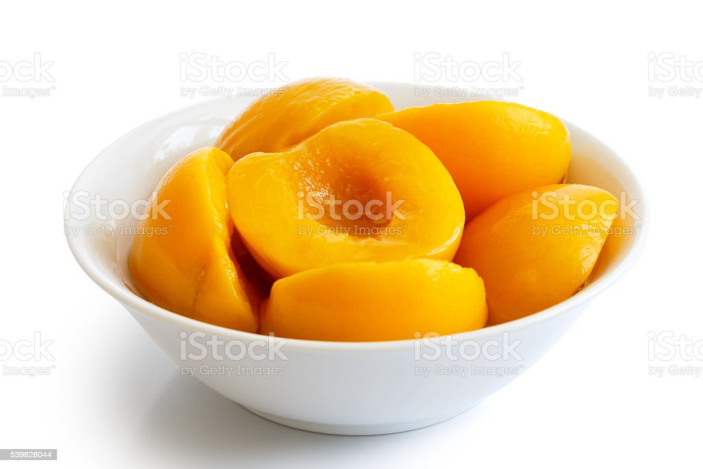 Canned peach halves in bowl isolated on white background. stock photo