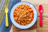 Canned children's meal spaghetti rings with meatballs and colorful utensils