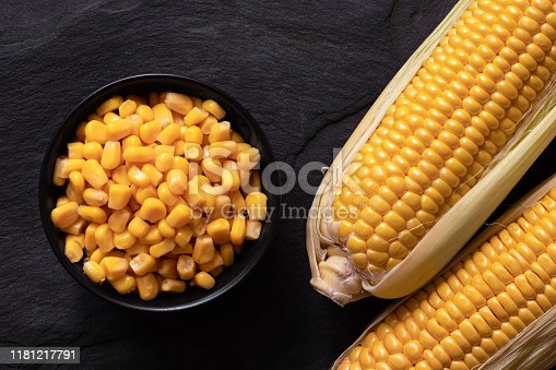 Canned sweet corn in a black ceramic bowl next to two corn cobs in husks on black slate. Top view.