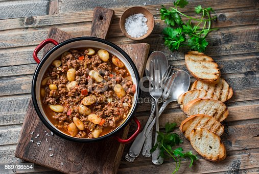 istock Cannellini beans beef slow-cooker stew on the wooden table, top view. Autumn, winter seasonal, healthy comfort food 869766554