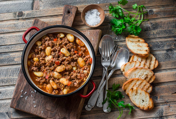 Cannellini beans beef slow-cooker stew on the wooden table, top view. Autumn, winter seasonal, healthy comfort food Cannellini beans beef slow-cooker stew on the wooden table, top view. Autumn, winter seasonal, healthy comfort food stew stock pictures, royalty-free photos & images