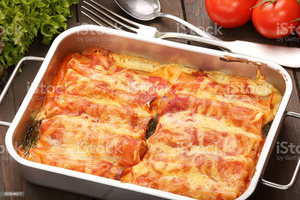 Cannelloni baked in a roasting pan on a wooden background stock photo