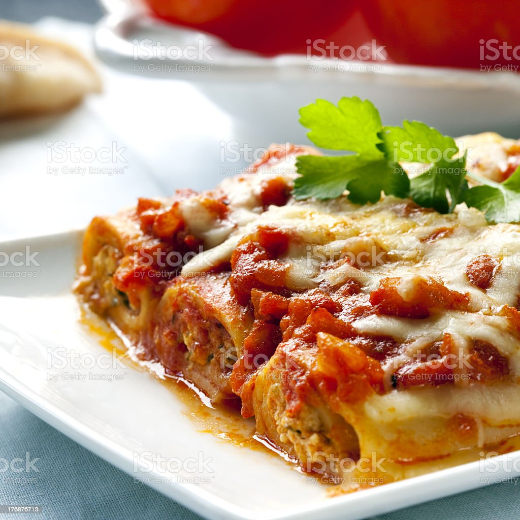 Cannelloni on a white plate on a table Cannelloni topped with melting cheeses, ready to enjoy. Bolognese Sauce Stock Photo