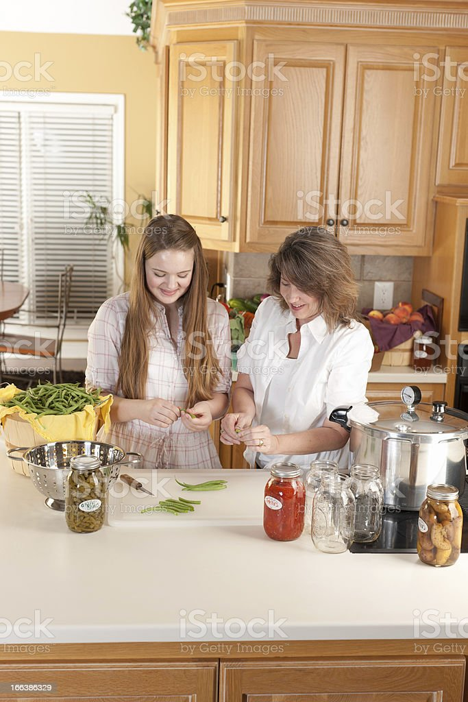 Canning: Caucasian Mother Teenage Daughter Preserving Homegrown Fruits Vegetables royalty-free stock photo