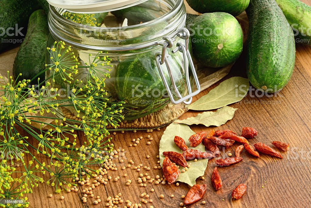 Canning green Cucumber with spices on wooden table stock photo