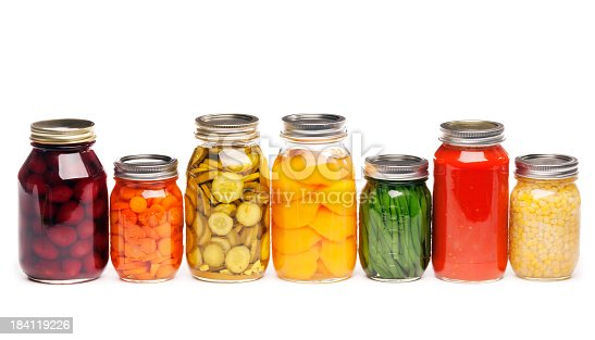 Horizontal straight-on view of a row of seven different canned vegetables and fruit, lined up in glass canning jars. The variety of vegetables that are sauced, pickled, or sliced include carrots, green beans, tomato sauce, corn, dill pickles, beats, and peaches, prepared for preserved storage. Isolated on a white background.