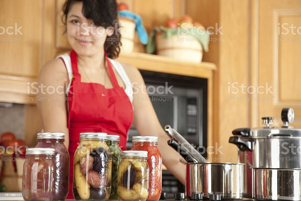 Canning: Mixed Race Young Adult Woman Preserving Homegrown Fruit Vegetables stock photo