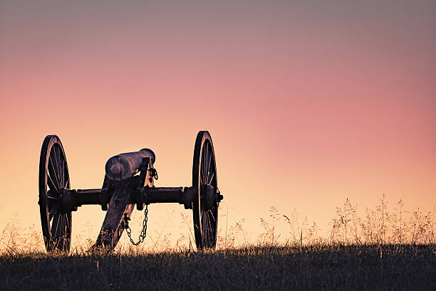 Cannon from Civil War at Sunset A cannon in Manassas Battlefield park lit by a setting sun. american civil war stock pictures, royalty-free photos & images