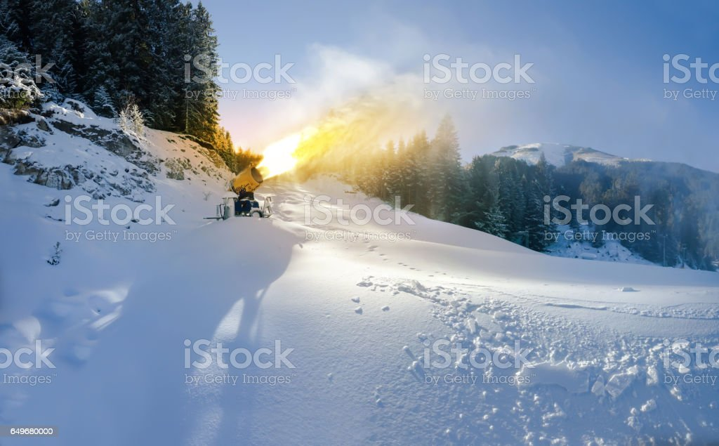 Cannon Gun making artificial Snow on Ski Slope against Sunset stock photo