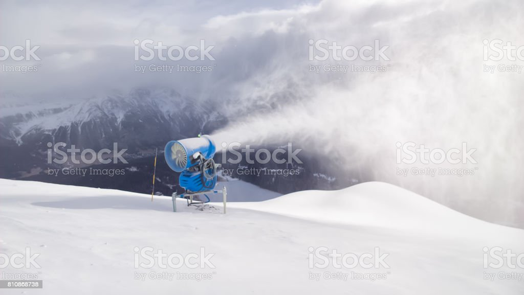 Cannon shoots snow in the Swiss Alps tourist area stock photo
