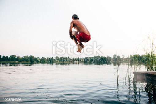 cannonball: rear view of a young man jumps into a lake