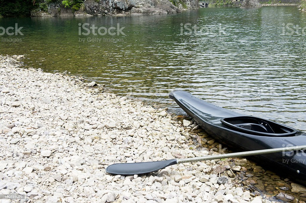 Canoe and oar by the river bank royalty-free stock photo