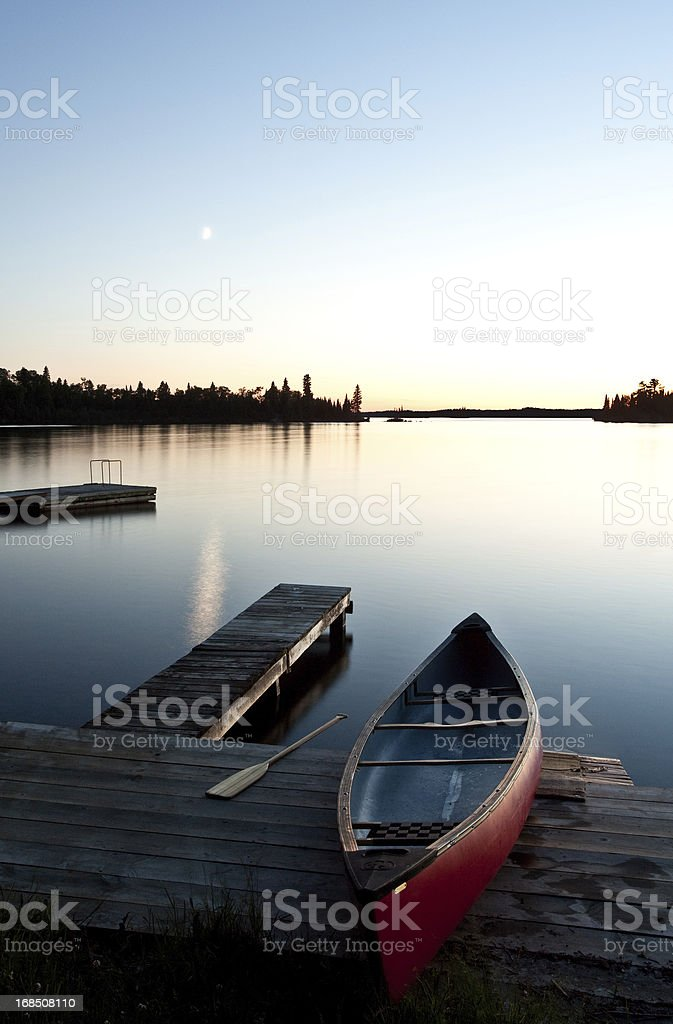 Canoe by a Dock at Sunset stock photo