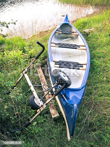 Canoe, Hobby, Adventure Sport - Canoe and its trailer left on the side of the river, ready to be ridden on its next adventure.