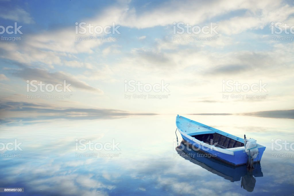 Canoe floating on the calm water under amazing sunset - foto stock