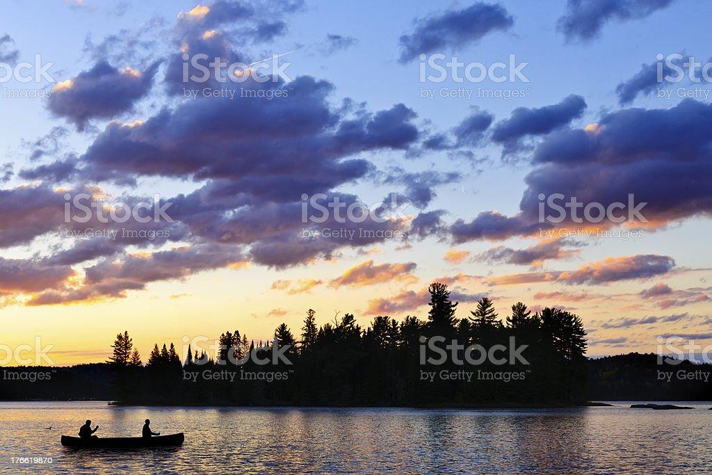 Canoe on lake at sunset stock photo