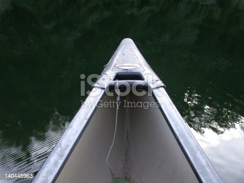 The bow of a canoe floats silently on a lake.