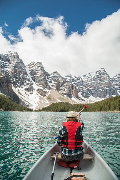 Canoe on Moraine Lake POV of Moraine Lake family canoeing. Canoeing in Banff National Park, Alberta, Canada moraine lake stock pictures, royalty-free photos & images