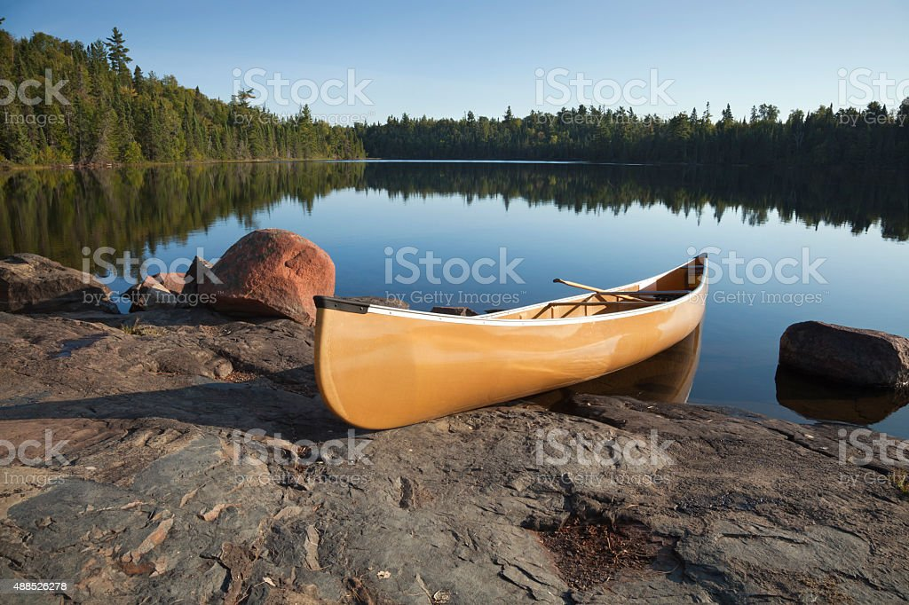 Canoe on rocky shore of calm lake with pine trees stock photo