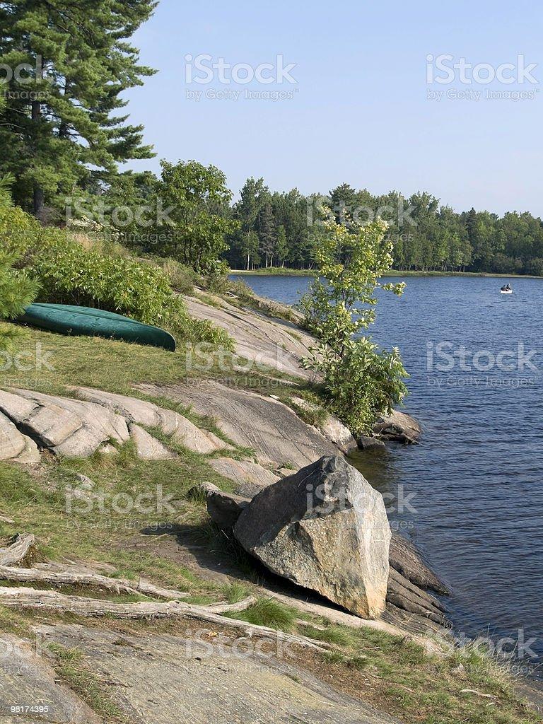 Canoa sul rive rocciose foto stock royalty-free