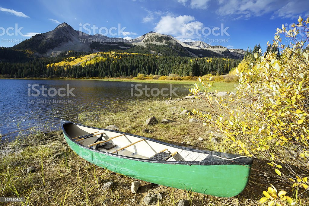 Canoe on the banks of Colorado Mountain Lake. stock photo
