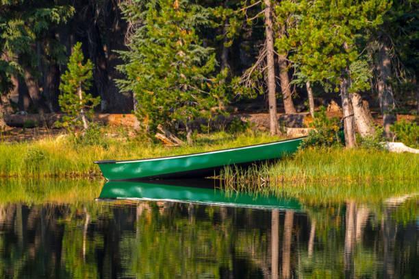 kanu auf dem rand des wassers auf einem reflektierenden see - boundary waters stock-fotos und bilder