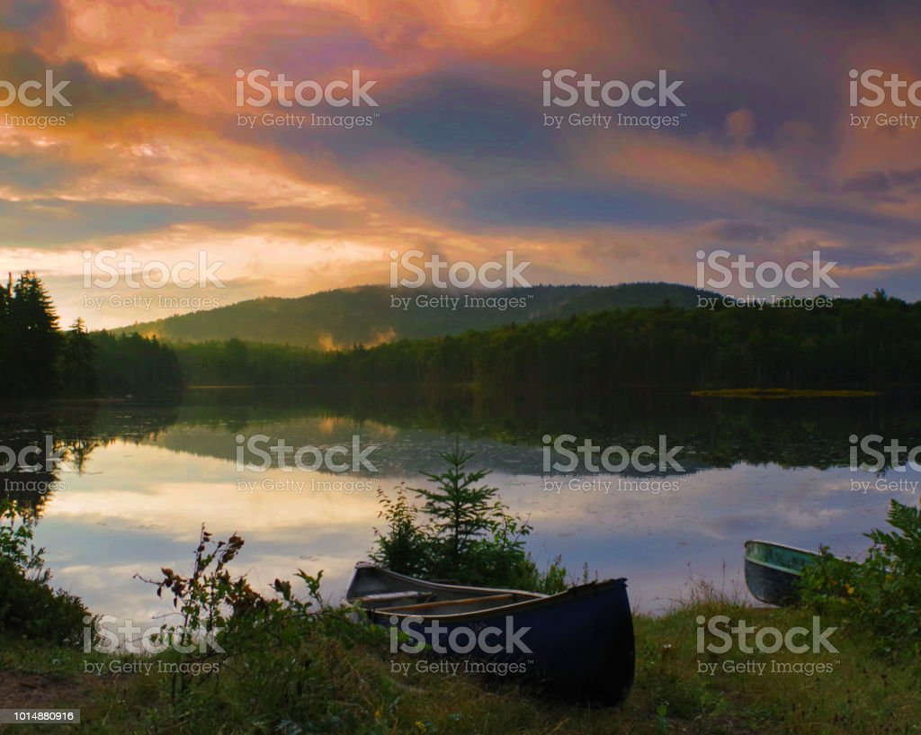 Canoe on the shore during a vibrant sunrise / sunset in the Adirondack Mountains. stock photo