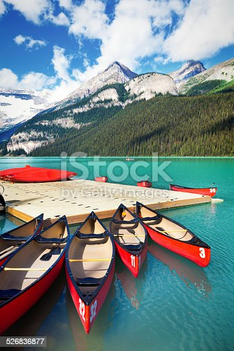 Canoe rental dock at Lake Louise in the Banff National Park of Canada, with its emerald water and mountain range of the Canadian Rockies.