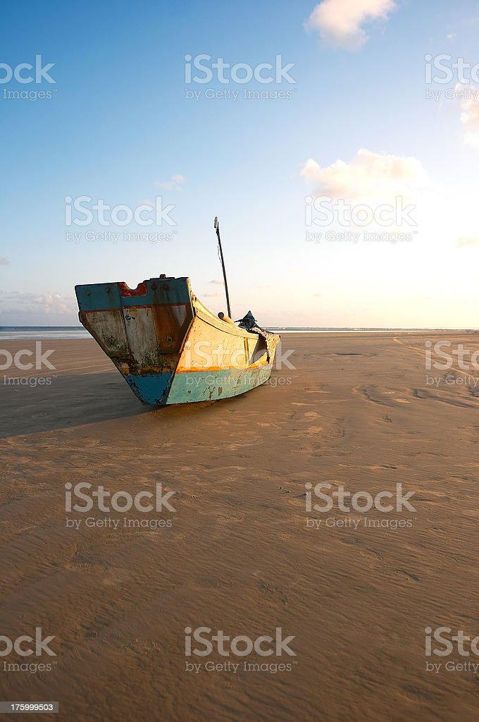 Canoe rests in the sand at sunset  (Brazil) royalty-free stock photo