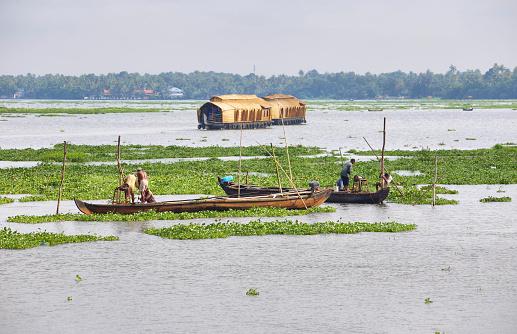 Kumarakon backwaters, India - September 24, 2019: Canoe with fishermen in the backwaters of Kumarakom early morning, Kerala, India.