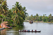 Allepey backwaters, India - September 23, 2019: Canoe with little students crossing the backwaters to go home in the backwaters of Allepey, Kerala, India.