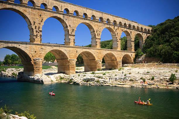 canoeing below pont du gard - pont du gard stockfoto's en -beelden