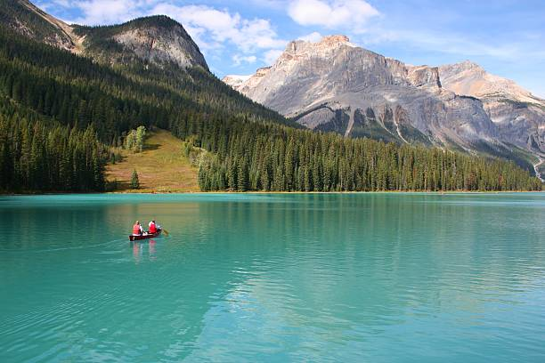 Canoeists on Emerald Lake Canoeists on Emerald Lake in the Canadian Rockies emerald lake stock pictures, royalty-free photos & images