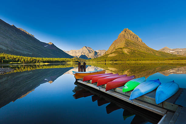 canoes at many glacier swiftcurrent lake glacier national park - us glacier national park stock pictures, royalty-free photos & images
