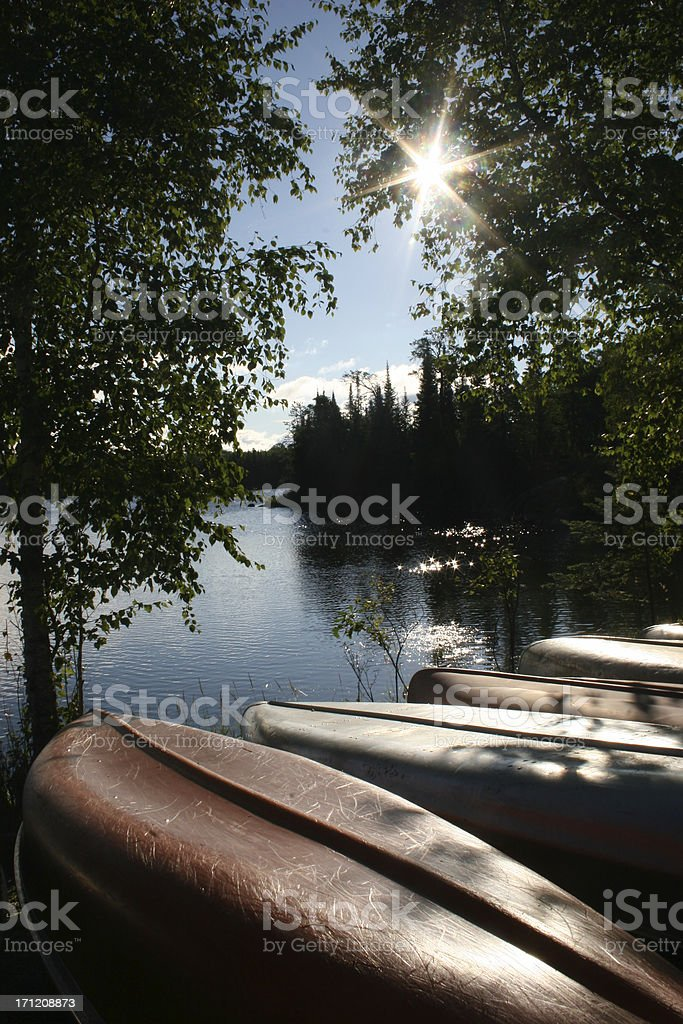 Canoes at the shore of a lake, sunlight coming through trees royalty-free stock photo