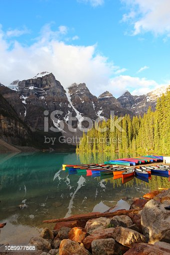 Calm Moraine Lake in the morning on a sunny summer day within the Canadian Rockies in Banff National Park, Alberta. Located in the Lake Louise area, this is one of the most famous travel destinations in the world and Canada.