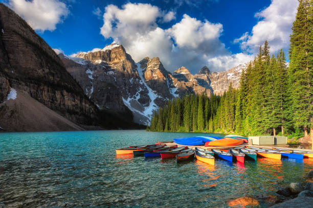 Canoes on Moraine lake in Banff national park, Canada Canoes on beautiful turquoise waters of the Moraine lake an sunrise with snow-covered peaks above it in Banff National Park of Canada canadian rockies stock pictures, royalty-free photos & images
