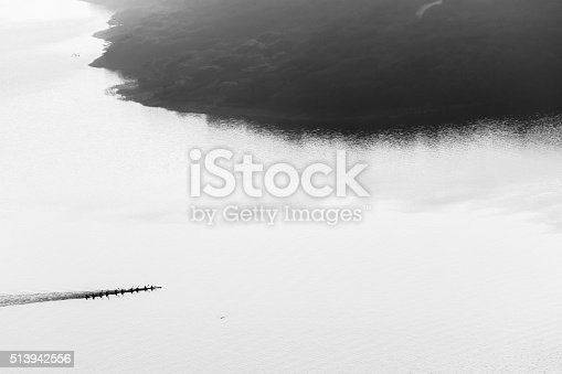Canoe Paddlers race across dam waters silhouetted birds-eye overhead air landscape in black and white vintage