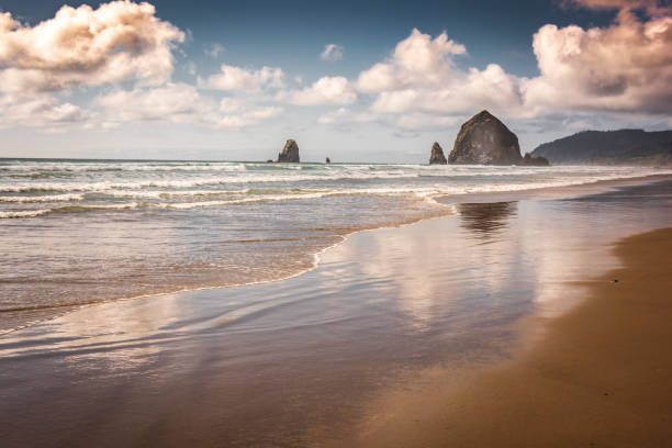Canon Beach Oregon Haystack Rock Reflections Clouds Tide Surf Beach Waves Sunset stock photo