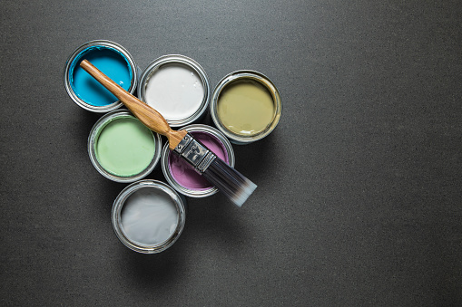 Cans of pastel coloured paint.