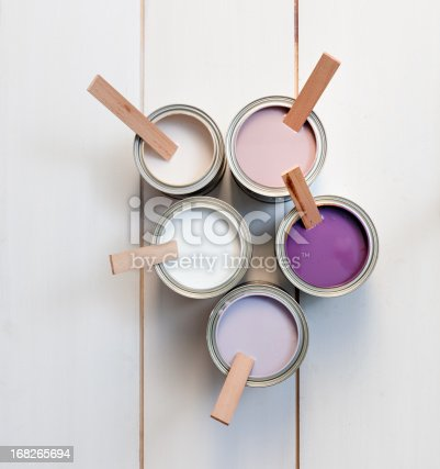 high angle view on five open paint cans with white, off white, purple, pink and lavender paint and wooden stirrers on wood laminate flooring
