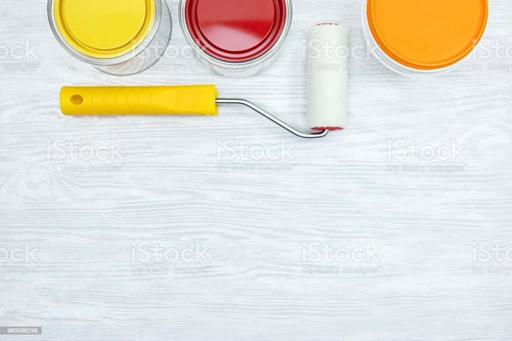 cans with yellow, orange and red paints and paint roller on grey wooden surface - Zbiór zdjęć royalty-free (Białoruś)
