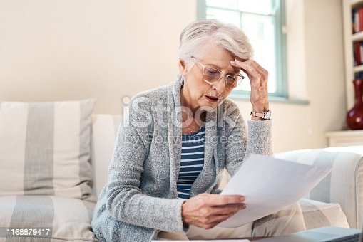 Shot of a senior woman looking stressed while going through paperwork at home
