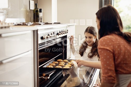 Shot of a little girl and her mother removing freshly baked cookies out of the oven