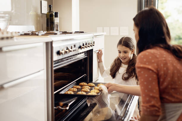I can't believe I did that! Shot of a little girl and her mother removing freshly baked cookies out of the oven oven stock pictures, royalty-free photos & images