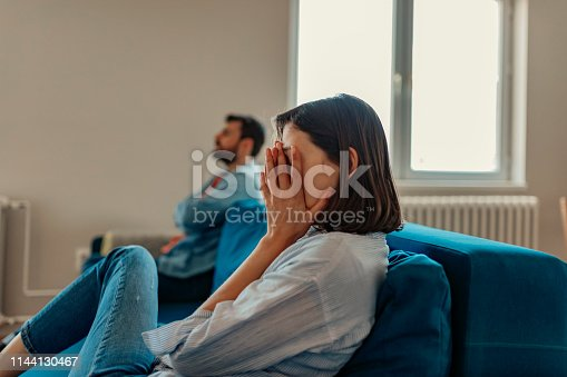 Unhappy Couple After an Argument in the Living Room at Home. Sad Pensive Young Girl Thinking of Relationships Problems Sitting on Sofa With Offended Boyfriend, Conflicts in Marriage, Upset Couple After Fight Dispute, Making Decision of Breaking Up Get Divorced