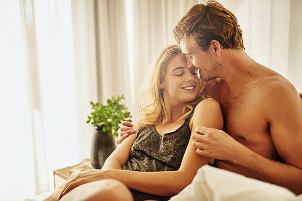 I can't get enough of your touch Shot of a young couple sharing an intimate moment  in bed real couples making love stock pictures, royalty-free photos & images