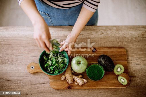 Woman preparing green smoothie at home on cutting board, directly above