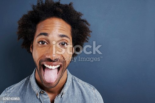 Portrait of a happy young man sticking his tongue out on a gray background