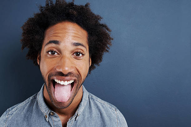 Can't hide the excitement Portrait of a happy young man sticking his tongue out on a gray background tongue stock pictures, royalty-free photos & images